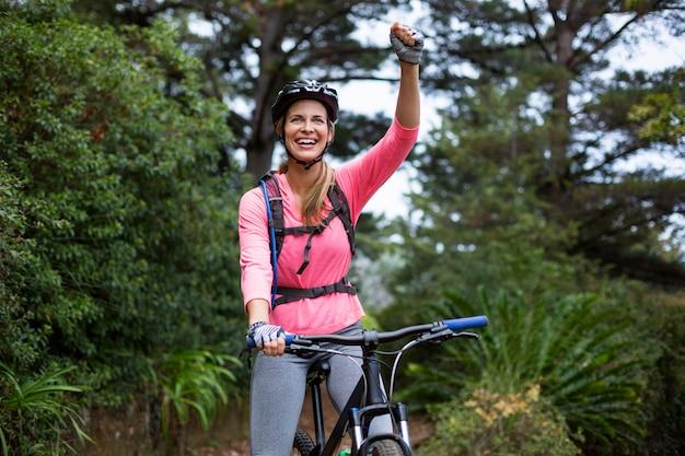 Mujer atlética de pie con bicicleta de montaña