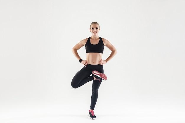 Mujer atlética de pie en una pierna, cogidos de la mano en el cinturón, sonriendo con dientes y mirando a la cámara. tiro del estudio