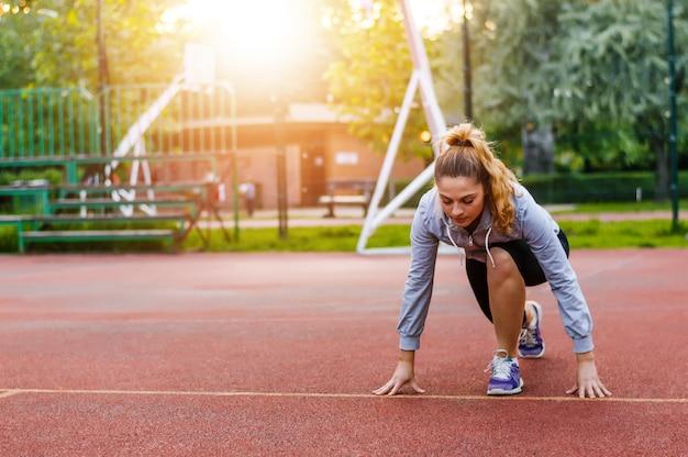 Mujer atlética en la pista de atletismo preparándose para comenzar a correr.