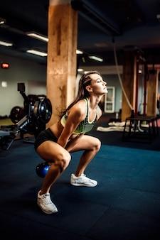 Mujer atlética que ejercita con la campana de la caldera mientras está en posición en cuclillas.