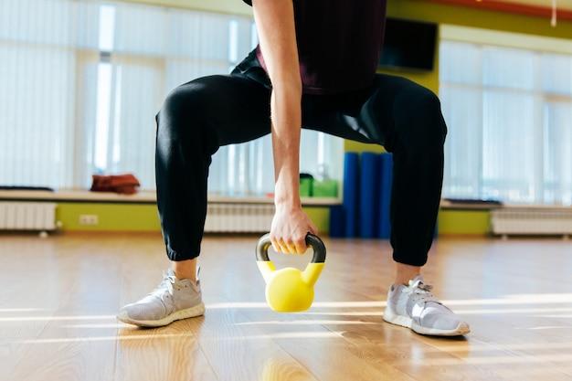 Mujer atlética que ejercita con la campana de la caldera mientras que está en la posición agazapada. mujer muscular que hace entrenamiento cruzado del ajuste en el gimnasio.