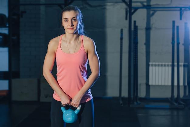 Mujer atlética que ejercita con la campana de la caldera mientras que está en la posición agazapada.