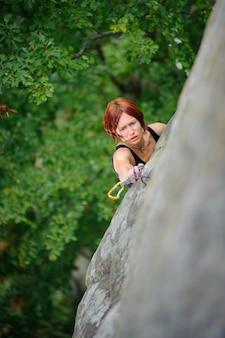 Mujer atlética que sube la pared del acantilado escarpado en tiempo de verano