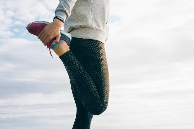Mujer atlética en ropa deportiva haciendo estirar las piernas