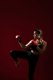Mujer atlética en ropa de fitness sobre fondo rojo