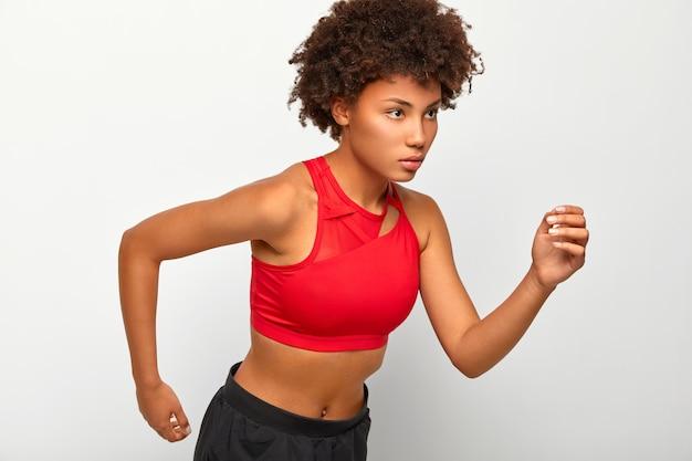 La mujer atlética segura de sí misma se para en pose de carrera, se ve seriamente en el final, demuestra resistencia, usa camiseta roja y pantalones cortos, se mueve activamente con los brazos