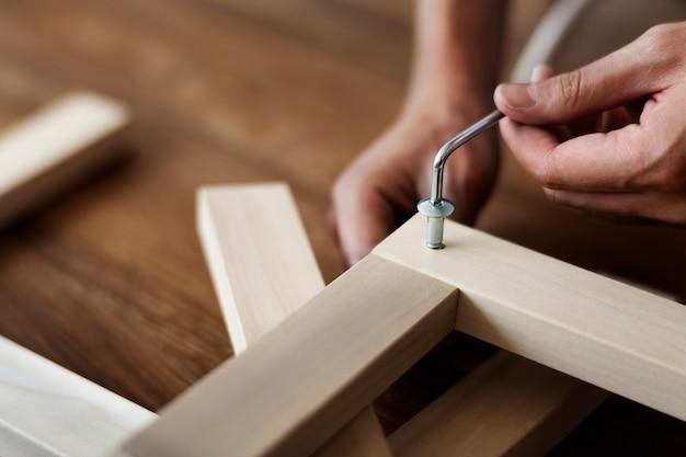Mujer atornillando la uña de la silla para muebles listos para ensamblar