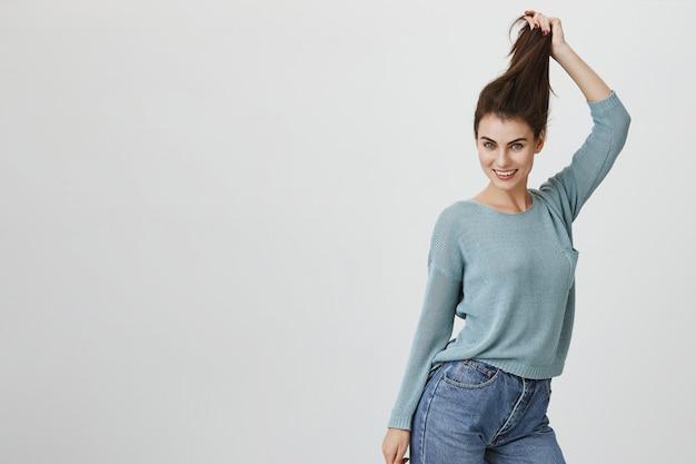 Mujer atractiva alegre que tira del pelo, anuncia productos para el cuidado del cabello