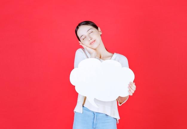 Mujer atractiva alegre sosteniendo el bocadillo de diálogo con forma de nube