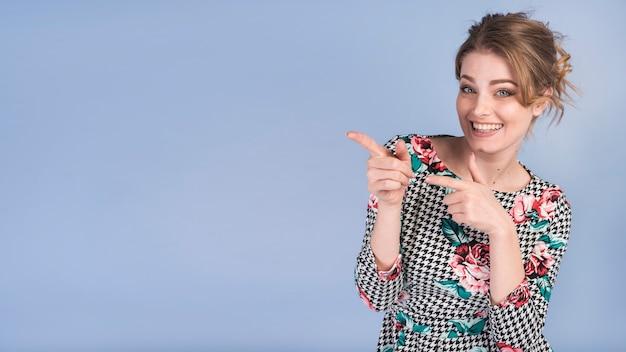 Mujer atractiva alegre en vestido elegante que señala en el lado