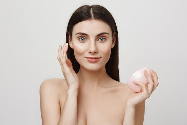 Mujer atractiva aplicar crema facial, producto anti-envejecimiento