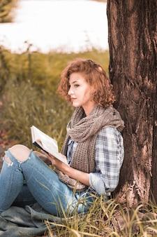 Mujer atractiva apoyándose en el árbol y sosteniendo el libro en el parque