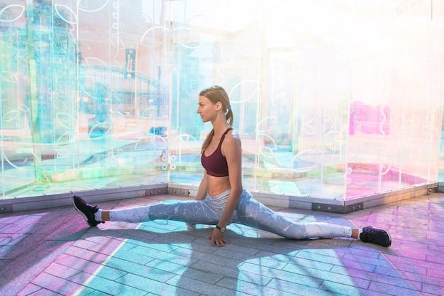 Mujer atractiva de la aptitud que realiza estirando ejercicio en el piso