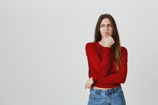 Mujer atractiva de aspecto serio pensando, haciendo una elección difícil
