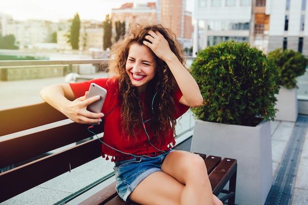 Mujer atractiva en auriculares con chat de video en línea con amigos usando un teléfono inteligente