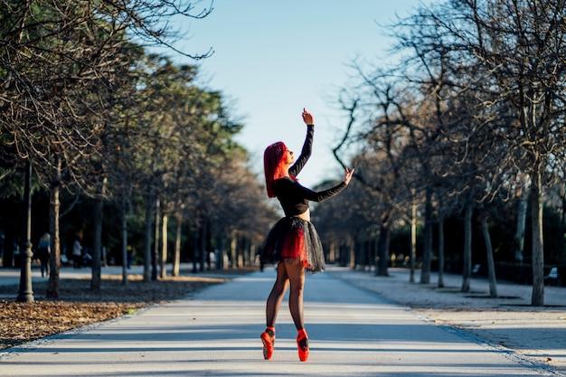 Mujer atractiva bailando ballet en un parque