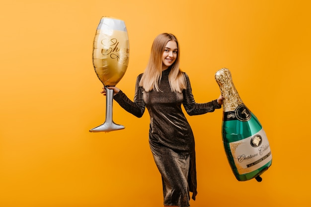 Mujer atractiva bailando en naranja con botella de champagne. retrato interior de jocund mujer caucásica celebrando un cumpleaños con vino.