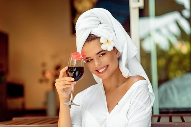 Mujer atractiva en una bata de baño blanca y una toalla con copa de vino y sonriendo a la cámara
