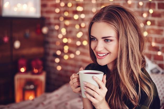 Mujer atractiva bebiendo té caliente