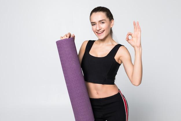 Mujer atractiva con bien en atuendo de gimnasio sosteniendo una estera en sus brazos extendidos aislado en la pared blanca
