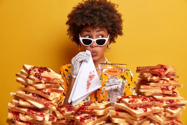 Mujer atractiva con cabello afro rodeado de sándwiches de gelatina de mantequilla de maní