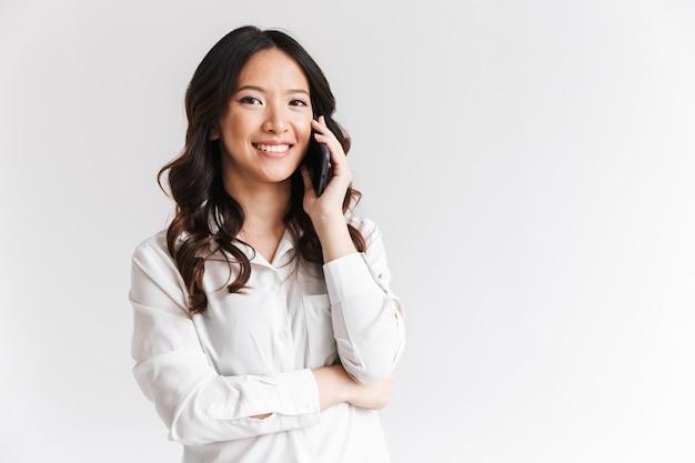 Mujer atractiva con cabello largo y oscuro con teléfono inteligente y llamada móvil