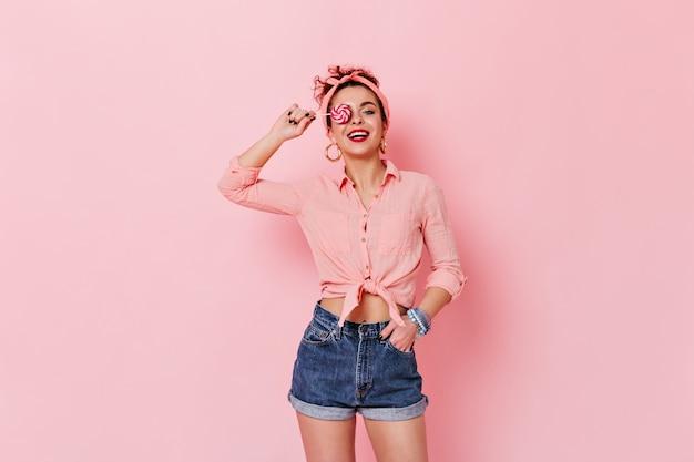 Mujer atractiva con camisa pin-up y diadema posando con piruleta en espacio rosa.