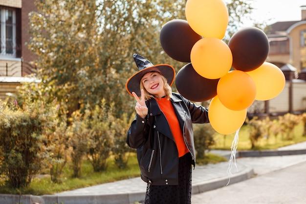 Mujer atractiva celebrando hallow al aire libre mostrando el símbolo de la victoria con una mano