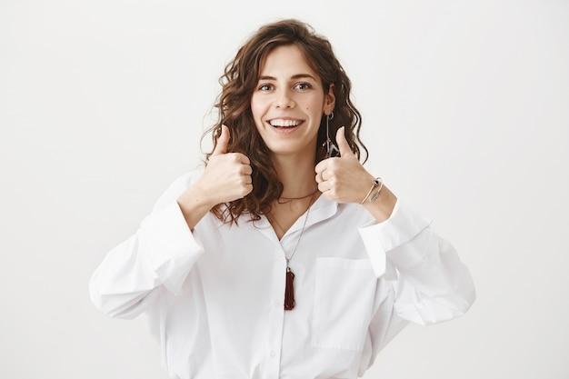 Mujer atractiva complacida con el pulgar hacia arriba en aprobación, recomendar producto