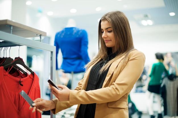 Mujer atractiva comprobando el código de barras en el centro comercial