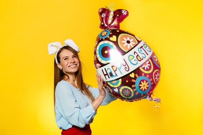 Mujer atractiva con orejas de conejo, jugando con globo de forma de huevo
