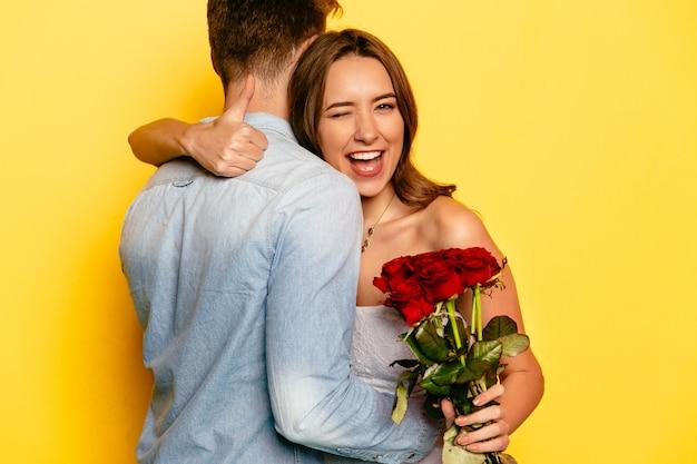 Mujer atractiva con rosas rojas guiñando un ojo y mostrando un pulgar mientras abrazaba a su novio.