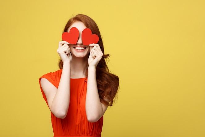 Mujer atractiva con sonrisa con dos pequeños corazones rojos en las manos cerrando los ojos