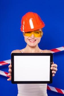 La mujer atractiva del constructor en la camisa blanca, el cinturón del constructor, el casco, los vidrios del constructor, los pantalones cortos de jean y las risitas sostienen la tableta vacía