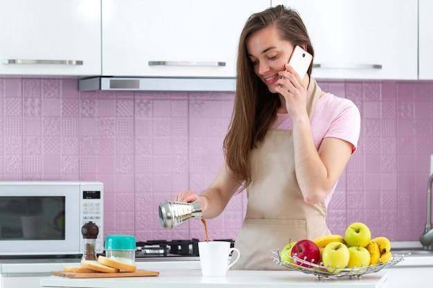 Mujer atractiva en delantal hablando por teléfono y haciendo café turco caliente de la mañana de cezve para el desayuno en la cocina