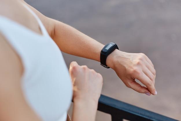 Mujer atractiva delgada sin rostro con top deportivo blanco que controla el dispositivo portátil de seguimiento de la salud y el estado físico, hace ejercicio, entrenamiento al aire libre, estilo de vida saludable
