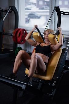 Mujer atractiva deportiva hermosa que hace entrenamiento agazapado en gimnasio