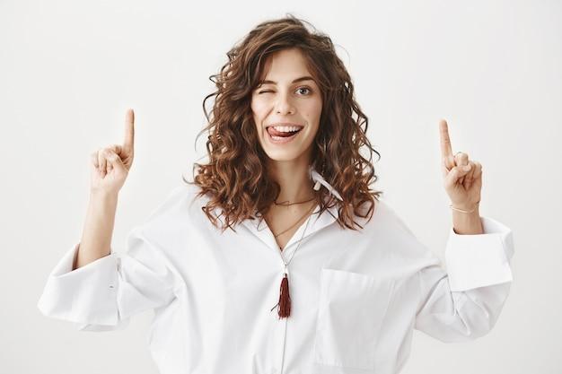 Mujer atractiva descarada guiña un ojo y muestra la lengua, apuntando con el dedo hacia arriba