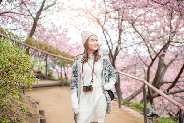 Mujer atractiva está disfrutando con cherry blossom en matsuda, japón