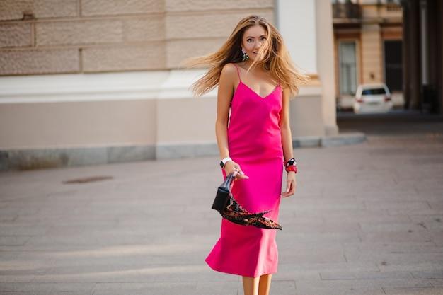 Mujer atractiva elegante sexy en vestido de verano sexy rosa pelo largo caminando en la calle sosteniendo el bolso