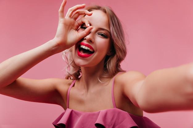 Mujer atractiva emocional con maquillaje brillante riendo en estudio