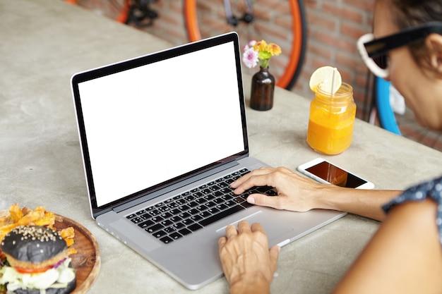 Mujer atractiva escribiendo o leyendo mensajes en una computadora portátil genérica con pantalla de espacio de copia para su contenido mientras envía mensajes de texto a amigos en línea
