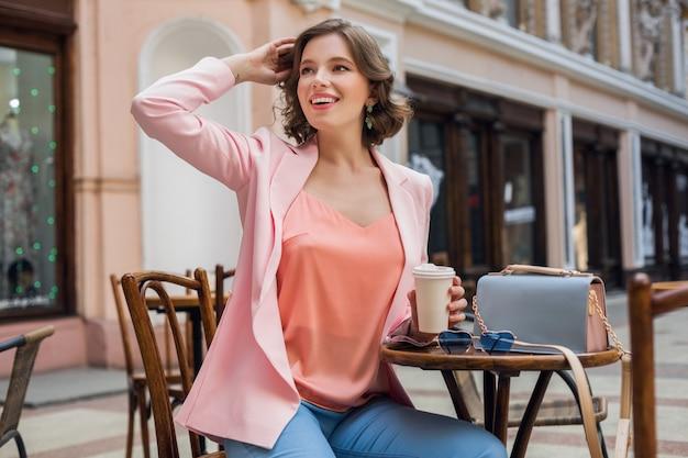 Mujer atractiva en estado de ánimo romántico sonriendo de felicidad sentada en la mesa con chaqueta rosa, ropa elegante, esperando novio en una cita en el café, bebiendo capuchino, expresión de la cara salida