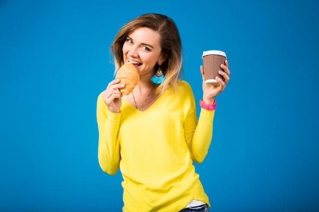 Mujer atractiva con estilo joven en blusa amarilla sobre azul