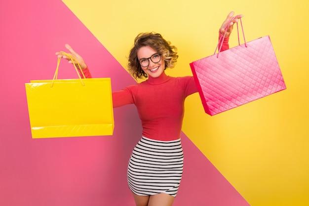 Mujer atractiva excitada en traje elegante y colorido sosteniendo bolsas de la compra con expresión de cara feliz emocionada, fondo amarillo rosa emocional, cuello polo, minifalda a rayas, venta, discout, adicto a las compras