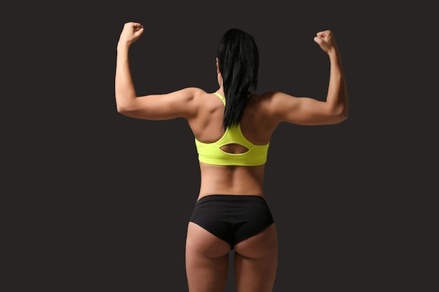 Mujer atractiva fitness en gris oscuro