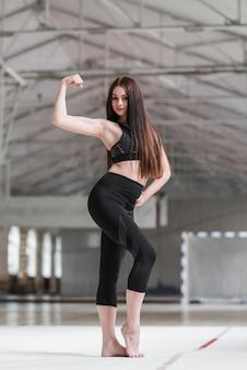 Mujer atractiva flexionando sus músculos en la clase de baile