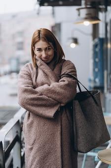 Mujer atractiva en gabardina en la calle de la ciudad