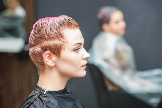 Mujer atractiva con glamour mojado corto cabello rosado en el salón de belleza.