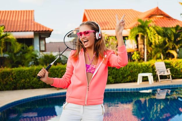 Mujer atractiva haciendo deporte en la piscina en colorida sudadera con capucha rosa con gafas de sol escuchando música en auriculares en las vacaciones de verano, jugar al tenis, estilo deportivo